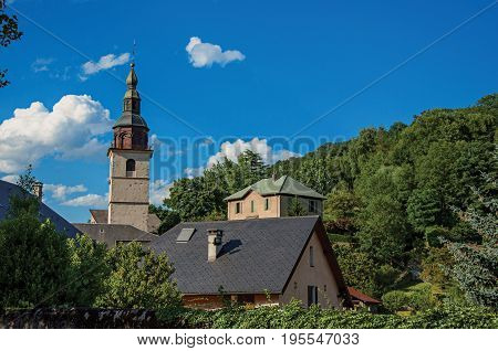 View of church steeple in the medieval village of Conflans, near the town of Albertville. Mountains landscape and blue sky on background. France