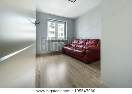 Red leather sofa in empty room with wooden floor