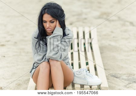 beautiful girl is conceived sitting on the beach
