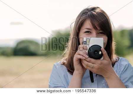 Lovely young long-haired girl with instant camera. She looks at you and smiles.