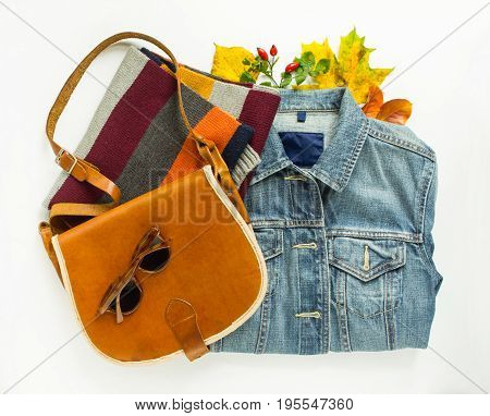 Stylish autumn look. Autumn fashion woman autumn outfit on white background. Blue denim jacket retro sunglasses red crossbody bag stripe scarf. Flat lay top view