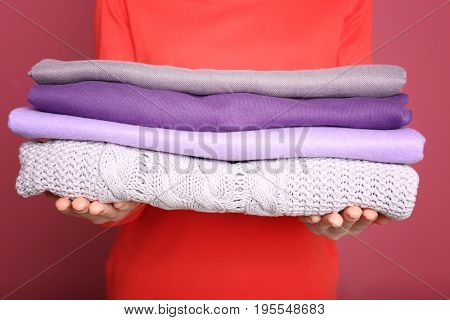 Woman holding stack of lilac clothes on color background
