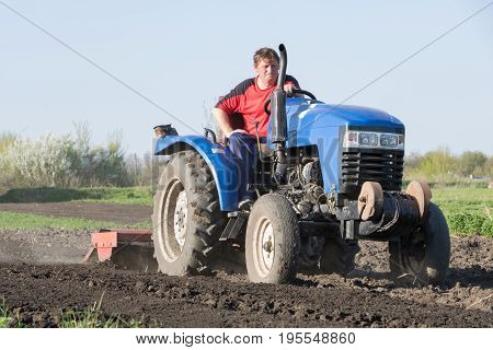 A farmer on a tractor lands a vegetable garden in the spring