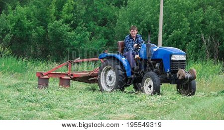 Man on a tractor mowing grass in a field
