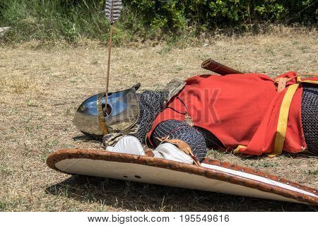 Medieval knight fallen in battle, with an arrow piercing his helmet and striking his head, reenactment with armor with chainmail, helmet swords and shields. Medieval demonstration and recreation