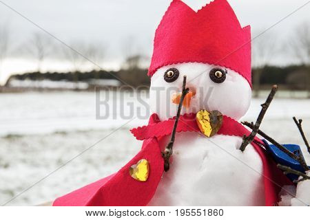 Cute snowmen dressed as a king with crown and cape looking very regal. Snow fall background in a rural winter scene