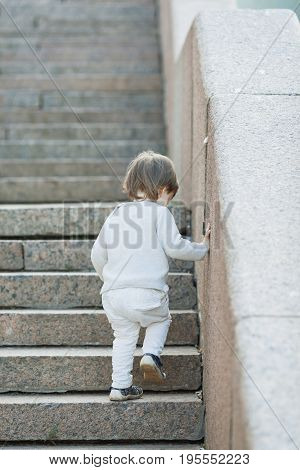 Little Blue-eyed Boy With Long Hair Climbs The Stone Stairs. The Concept Of Growing Up