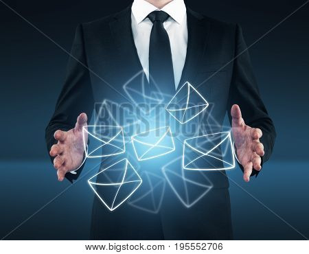 Businessman holding glowing digital letters on dark blue background. Email marketing concept