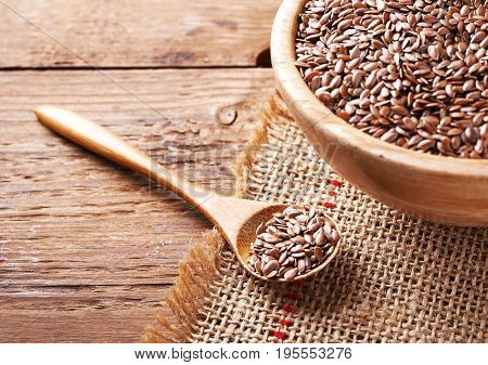 flax seeds in spoon on wooden background.