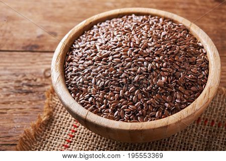 flax seeds in bowl on wooden background.