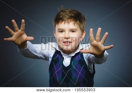 Portrait of angry boy isolated on gray background. He raised his fist to strike.