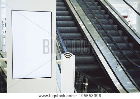 Close up of blank poster in shopping mall with escalator. Mock up