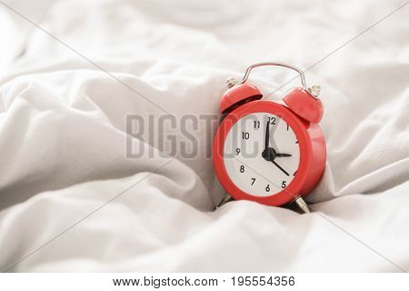Red alarm clock in a bed