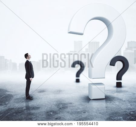 Side view of young adult businessman looking at question marks on abstract foggy gray background. Questionnaire concept. 3D Rendering
