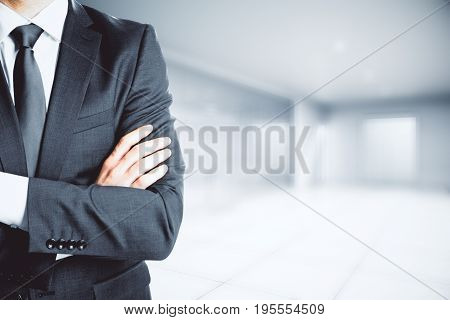 Businessman with folded amrs standing in blurry office interior. Copy space. Lifestyle concept. 3D Rendering