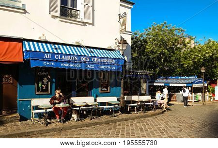 PARIS , France- July 14, 2017: View of typical paris cafe in Paris. Montmartre area is among most popular destinations in Paris, Au clairon de chasseur is a typical cafe.