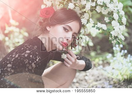 woman with fashionable makeup and red lips has rose flower in hair hispanic or spanish style in black dress at white spring or summer blossom on natural background