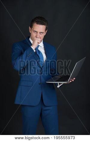 manager with hand near face in blue formal suit on dark background. Overworked businessman with laptop or computer. Technology for business. Stress and problems. Working hard