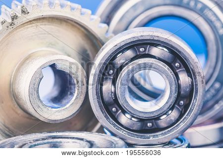 Group of various ball bearings and gears close up on nice blue background with reflections.