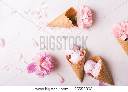 Ice cream in a waffle cone on a light background. Strawberry ice cream. Flowers in a waffle cone. Pink carnations. Flowers on a wooden background. Copyspace. Flower photo concept