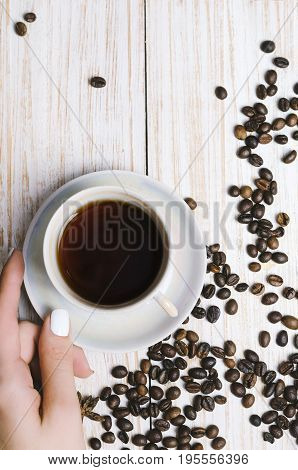 Cup of coffee and coffee beans on white wooden background.