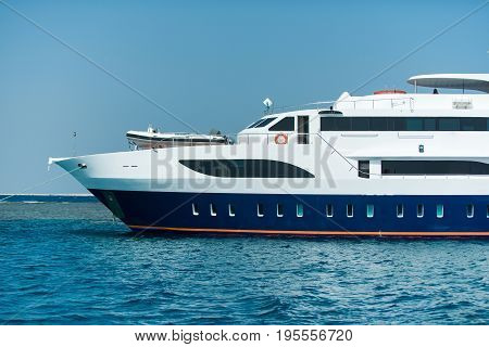 Cruise ship half of big white beautiful vessel transport for summer vacation tour voyage on background of blue ocean water and sky