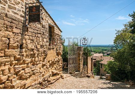 Châteauneuf-du-Pape, France, July 02, 2016. Alley of stones, wall and gate in the city center of the Châteauneuf-du-Pape hamlet. Near Avignon, Vaucluse department, Provence region, southeastern France