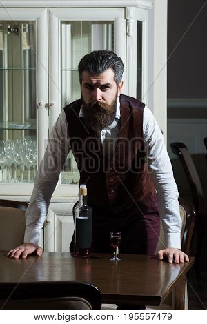Man Standing At Table Served With Glass And Bottle