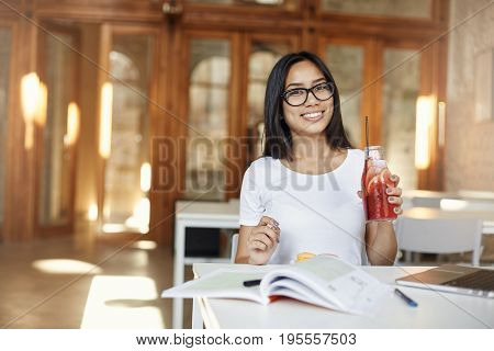 Young female student taking a break from classes sitting in a cafe using laptop and doing homework drinking lemonade. Education concept.
