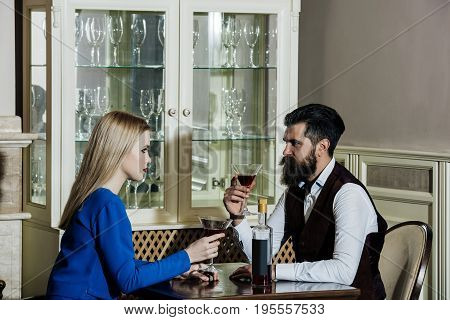 Girlfriend and boyfriend drinking red wine in restaurant. Girl or woman and man or hipster sitting with martini glasses at table. Couple in love. Date dating. Alcohol appetizer. Addictive convive
