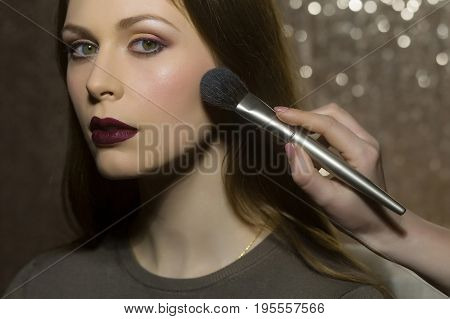 professional makeup artist working with beautiful young woman on glowing background fashion victim