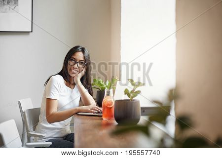 Young and smart entrepreneur running her online business from nearby cafe drinking lemonade and enjoying profits.