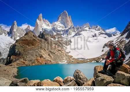 Male trekker resting on the rock in front of the stunning and impressive Mount Fitz Roy near El Chalten in Patagonia, Argentina