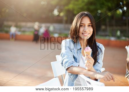 Girl eating icecream in park on a sunny summer day smiling looking at camera enjoying the taste.