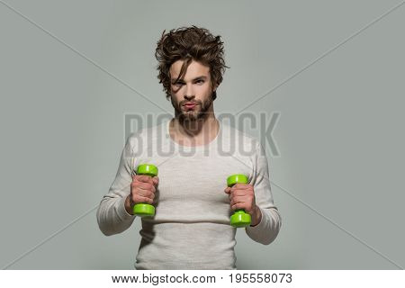 guy with barbell or dumbbell workout has disheveled and uncombed long hair and beard on face in white underwear on grey background morning exercise and wake up barbershop sport