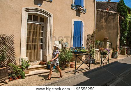 Châteauneuf-du-Pape, France, July 02, 2016. Street view with stone houses and woman in the center of Châteauneuf-du-Pape hamlet. Near Avignon, Vaucluse department, Provence region, southeastern France