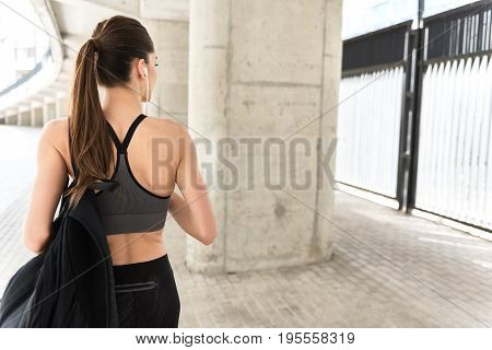 Pensive female athlete is resting after exercising. She is wearing earphones and listening to music. Focus on her back carrying rucksack. Copy space