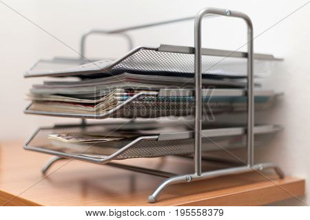 Metal drawers briefcases with newspapers and magazines on wooden table