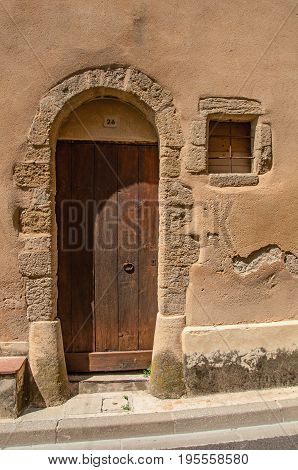 Châteauneuf-du-Pape, France, July 02, 2016. Street door made of wood on old stone wall in the Châteauneuf-du-Pape hamlet. Near Avignon, Vaucluse department, Provence region, southeastern France