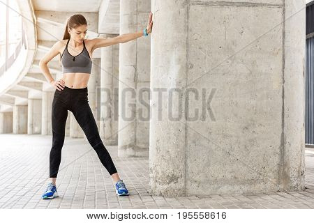 Full length portrait of confident sporty girl undergoing warm-up before jogging. She is leaning on wall by stretching hands and looking down at leg pensively. Copy space in right side