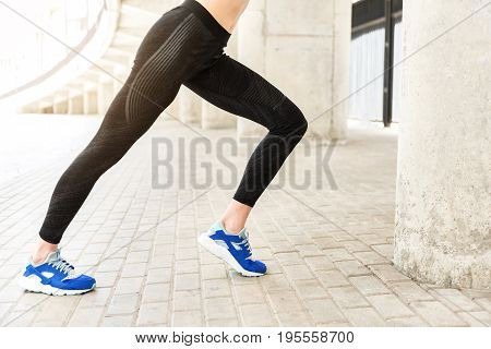 Close up of strong muscular female legs. Young woman is warming up before jogging