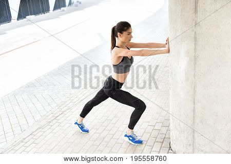Side view of confident fit girl doing push-ups while standing and leaning arms on column. She is looking forward with aspiration. Copy space in left side