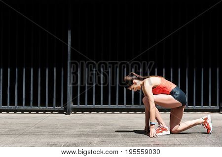 Serious female runner is standing in starting position. Girl is kneeling and looking down with concentration. Copy space in left side
