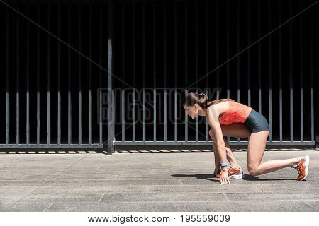 Ready to run. Confident young woman is kneeling at start posture. She is looking forward with aspiration. Copy space
