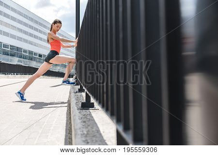 Low angle of slim calm young woman warming up before running. She is leaning leg on a curb while stretching other one behind. Copy space