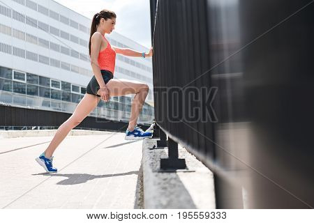 Low angle of confident female runner training her body for marathon. She is leaning leg on concrete border and arm on fence. Girl is looking forward with aspiration