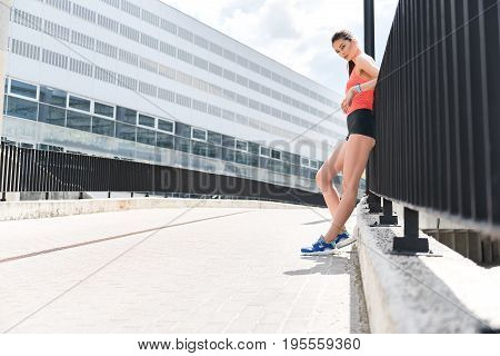 Relaxing after workout. Calm young woman is standing outdoors and leaning on fence. She is looking forward with interest. Copy space in left side. Low angle