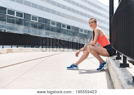 Thinking about success in sport. Portrait of dreamful young woman relaxing after jogging outdoors. She is sitting near fence and laughing. Copy space