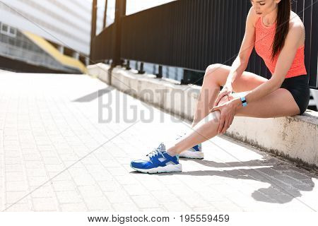 My leg hurts after jogging. Upset young girl is touching her knee while sitting near fence outdoor. Copy space in left side