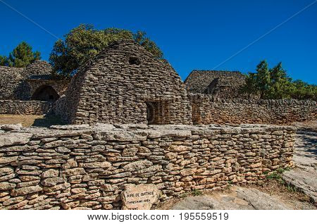 Typical hut made of stone with walled fence and sunny blue sky, in the Village of Bories, near the town of Gordes. Vaucluse department, Provence region, in southeastern France